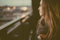 遠くを見つめ考え込む女性
